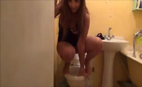 Beautiful shaved teen pooping over toilet