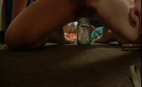 Sexy amateur girl peeing in a glass jar