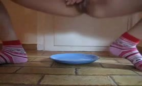 Shaved girl pooping on a plate