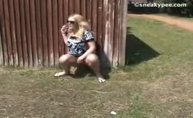 Blonde girl peeing outdoor