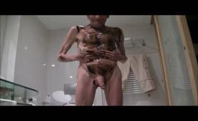 Skinny guy rubbing brown poop on his body