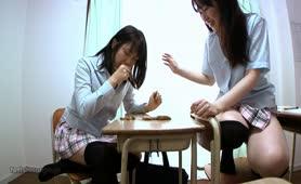 Two Asian school girls tasting poop