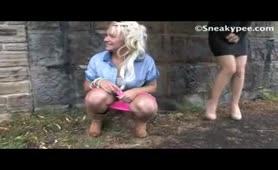 Three girls peeing under a bridge